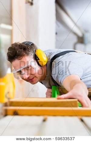 Carpenter working on an electric buzz saw cutting some boards, he is wearing safety glasses and hearing protection for workplace safety
