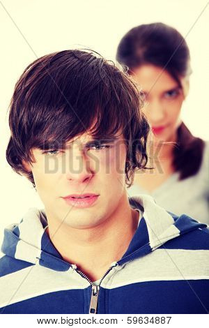Young beaten up caucasian man standing in front of angry young woman. Couple fight. Isolated on white