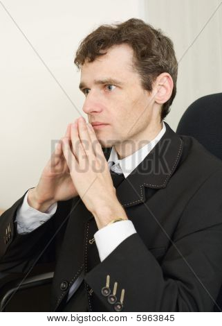 Guy In Black Jacket Sits Having Combined Hands