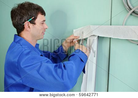 A man prepares a new window frame for installation in a window aperture
