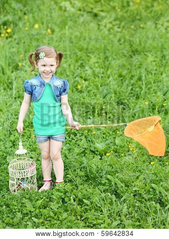 Little pretty girl stands with butterfly net and coop on green meadow.