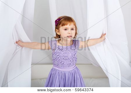 Little girl dressed in holiday clothes looks out from under tent over bed
