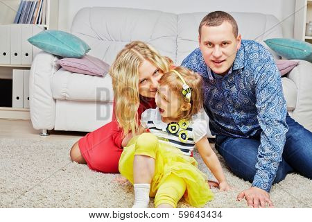 Family of three sits on carpet in light room, daughter ahead, parents behind, mother whispers something at daughter ear