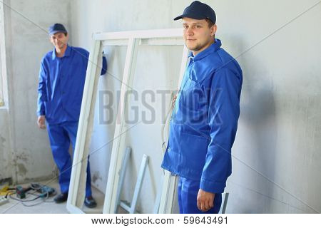 Two men in work clothes with the new window frame in a room under renovation