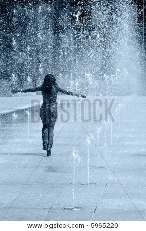 Young Girl Running Under The Water Of A Fountain