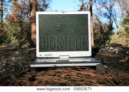 An old well used and probably broken laptop computer sits on top of an outdoor fire pit in preparation to be doused with gasoline and light on fire for an amazing Stock Photo opportunity.