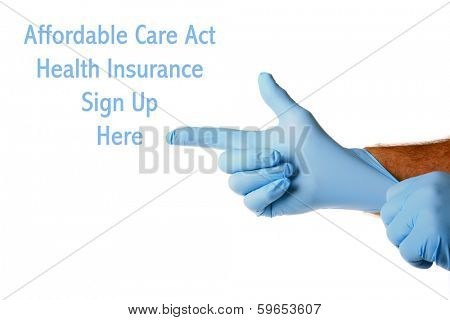 A Genuine Doctor points to the Affordable Care Act Health Insurance Sign Up Here text as he puts on his blue latex exam gloves. Isolated on white with room for your text or images