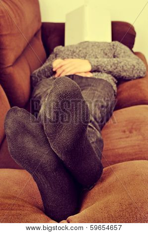 man taking a nap in a couch with a book covering his face