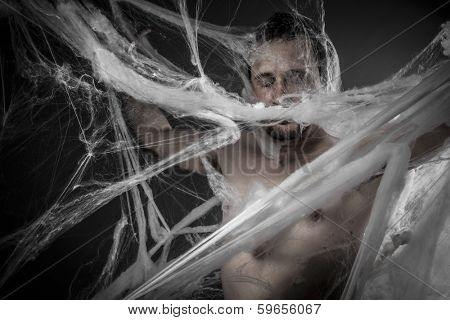 Geometry.man tangled in huge white spider web
