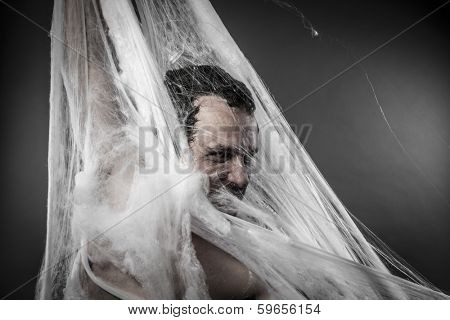 Night.man tangled in huge white spider web