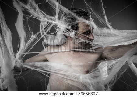 Scary network.man tangled in huge white spider web