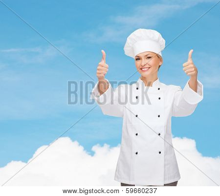 cooking, gesture and food concept - smiling female chef, cook or baker showing thumbs up