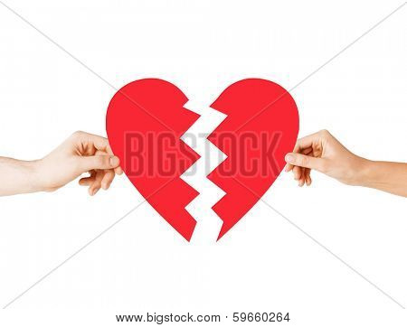 love and relationship problems concept - male and female hands holding two parts of broken heart