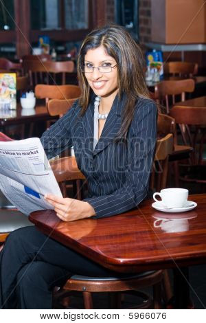 Businesswoman reading newspaper