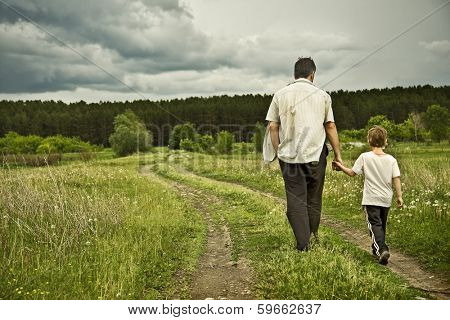 boy and his father are on the road away