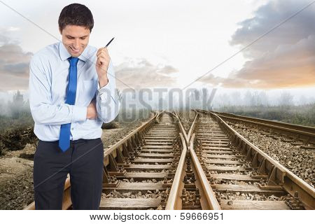 Thinking businessman holding pen against railway tracks leading to misty forest
