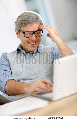 Happy businessman reading good news on laptop