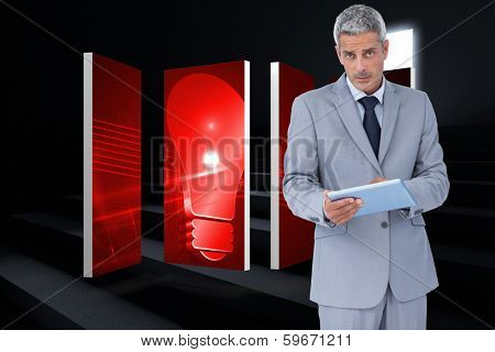 Serious businessman using tablet pc looking at camera against steps leading to light in the darkness