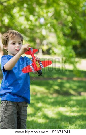 Cute young boy with toy aeroplane standing at the park