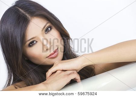Portrait of a beautiful young Chinese Asian Oriental woman resting on her hands