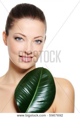 Beautiful Smiling Woman With Green Leaf Near Her Face