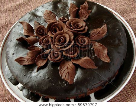 homemade glazed cake decorated with chocolate roses and leaves