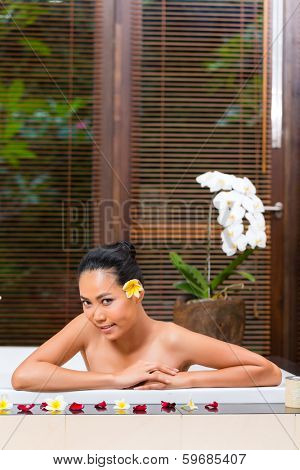 Indonesian Asian woman in wellness beauty day spa having aroma therapy bath with essential oils or salt, looking relaxed
