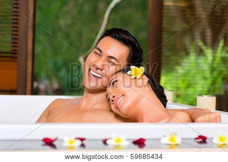 Indonesian Asian couple in wellness beauty day spa having aroma therapy bath with essential oils or salt, looking relaxed