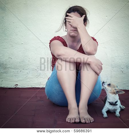 Desaturated grunge image of a very sad adult woman crying (with a small dog besides her)