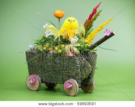Wicker cart with Easter chickling and eggs over light green background