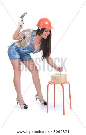 Woman in orange helmet hammer in nail
