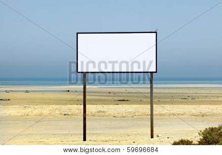 A large sign on an idyllic beach with no text and a small bird - a Southern Grey Shrike - perched on one corner.