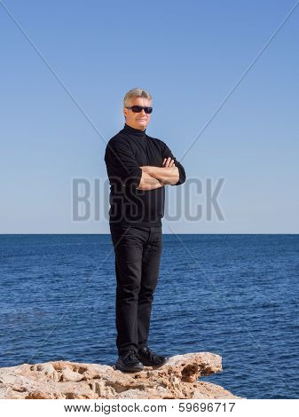 Confident Handsome Business Man Standing On A Rock
