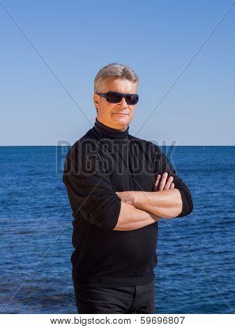 Confident Businessman In Black Posing On The Seashore