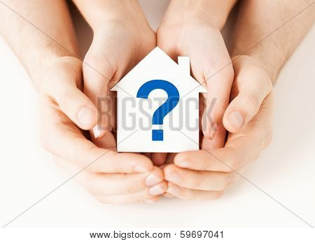 real estate and family home concept - male and female hands holding paper house with question mark
