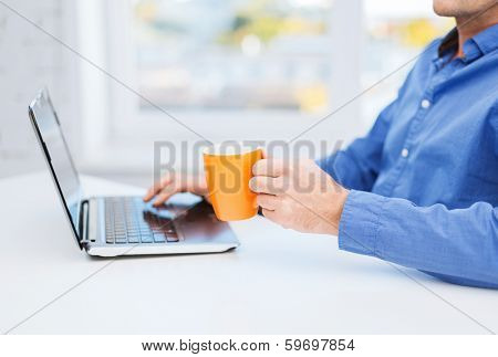 technology, beverage and lifestyle concept - close up of male hand holding cup of warm tea or coffee with laptop computer
