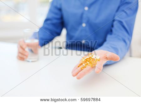 health, healthcare, medicine, medication and drugs concept - close up of male hand showing lot of pills