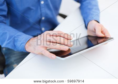 technology and internet concept - close up of male hands working with tablet pc computer