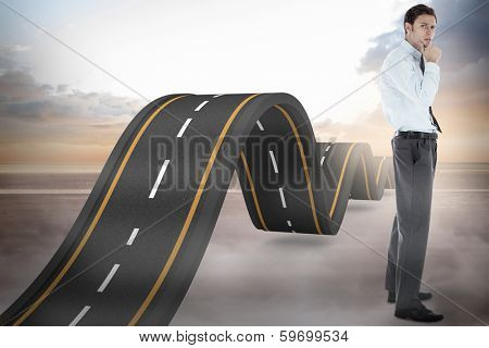Thoughtful businessman with hand on chin against bumpy road backdrop