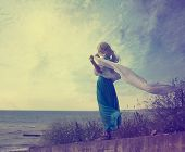 stock photo of lonely  - Vintage Photo of Lonely Woman with Waving Scarf at the Sea - JPG
