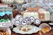 foto of fancy cakes  - Homemade fancy set table with sweets candies cake marshmallows zephyr nuts almonds truffle as a present for birthday party - JPG
