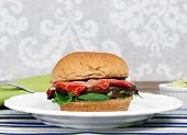 image of portobello mushroom  - Healthy portobello mushroom burger on a whole wheat roll with roasted peppers provolone cheese and greens - JPG