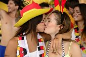 stock photo of lesbian  - Cheerful couple of German lesbian soccer fans kissing each other celebrating victory - JPG