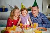 stock photo of snuff  - Family of three sits at birthday table - JPG