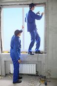 Two men in working clothes set new window frame, one of them standing on the windowsill and fastens