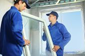 stock photo of carpenter  - Two workers in blue work clothes set a new window in the window frame - JPG