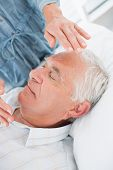 stock photo of reiki  - Closeup of senior man receiving Reiki treatment by therapist at health spa - JPG