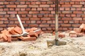 Shovel and pickaxe on a construction site, brick wall background