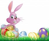 stock photo of hare  - Pink Easter eggs bunny rabbit with a wicker basket full of chocolate painted Easter eggs - JPG