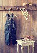 stock photo of dungarees  - Nursery with toy plane and animal figures with hanging dungarees - JPG